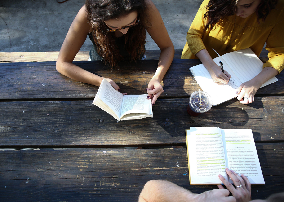 Two college girls studying at a picnic table outside with their notebooks and pens