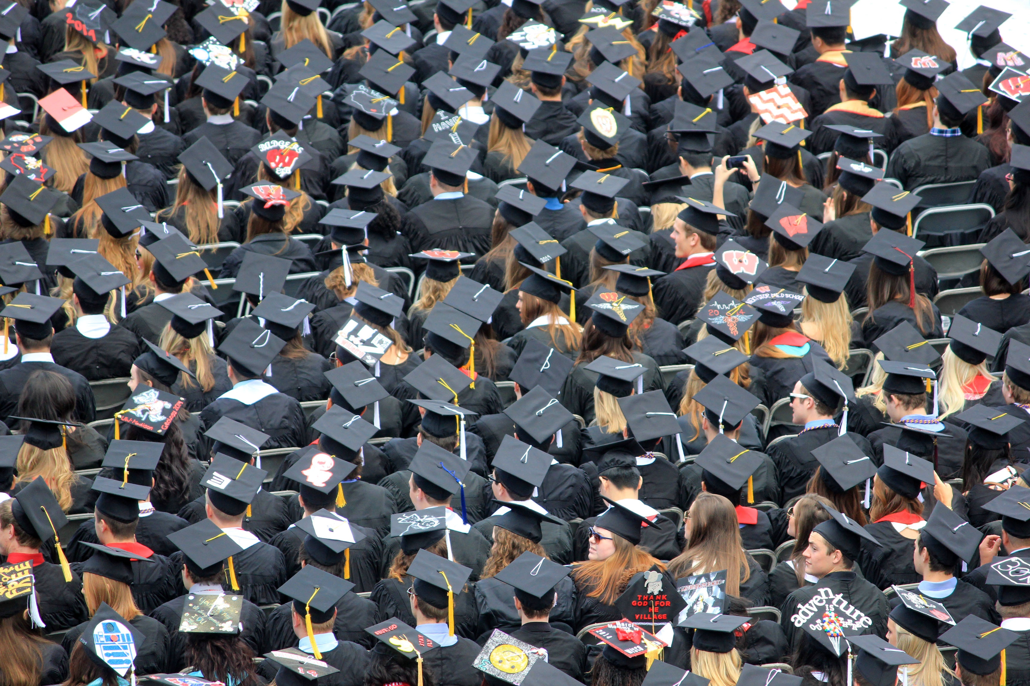 A sea of college or university graduates in caps and gowns on graduation day