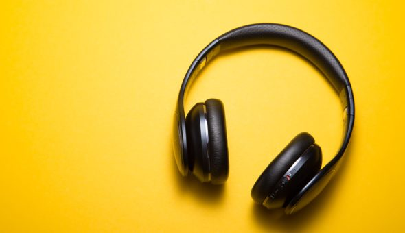 A pair of black headphones against a plain yellow background